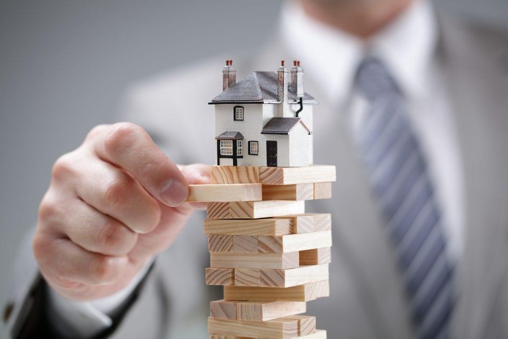ilustação de homem segurando um lego de imóvel, para falar sobre fundos imobiliários