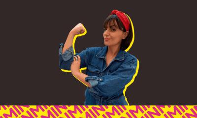 """Paula Reis fazendo o gesto """"We can do it"""" com um fundo preto"""