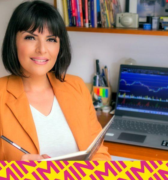 Paula Reis sentada em frente ao computador, segurando um caderno e uma caneta