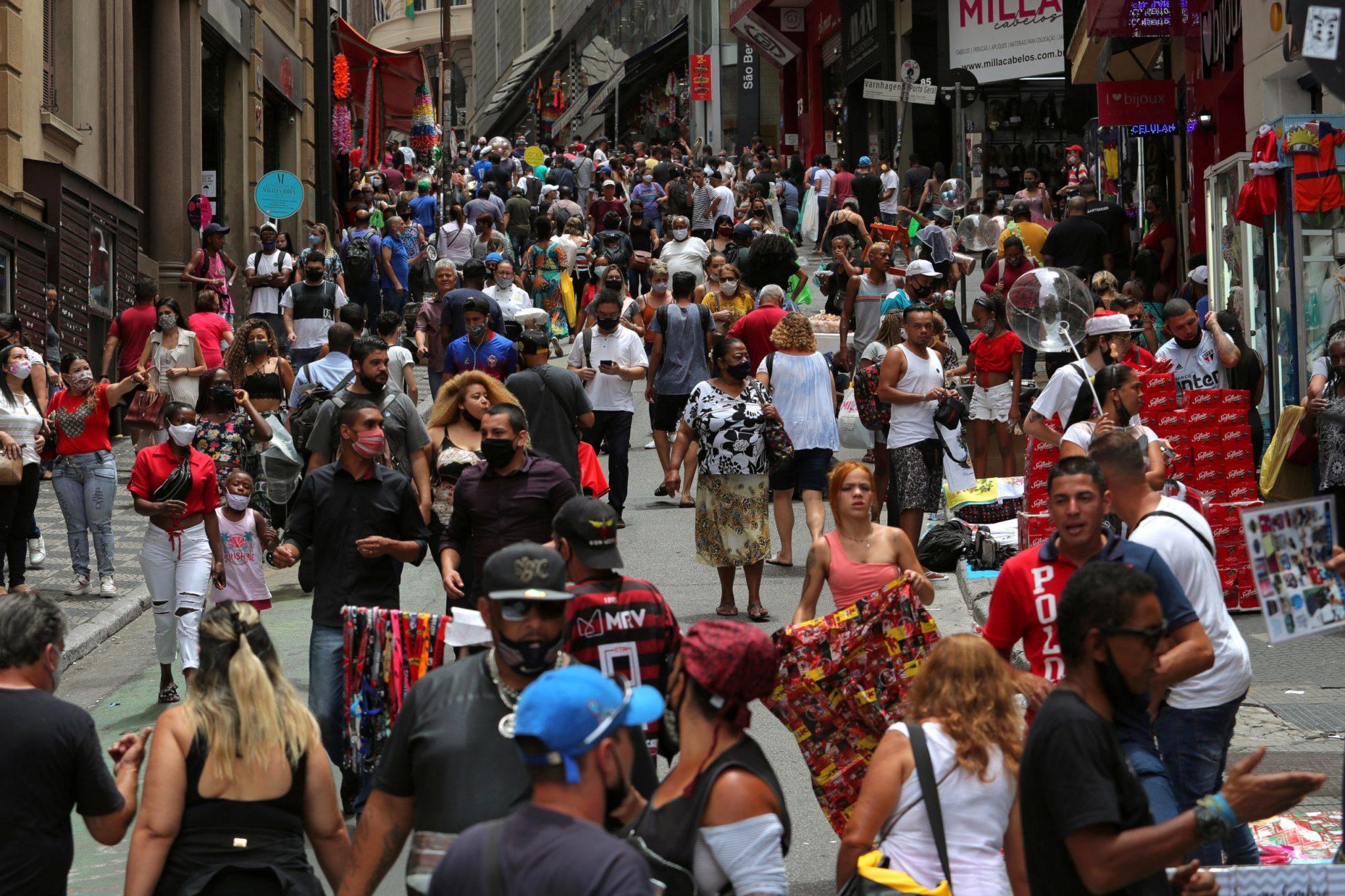 Pessoas caminham em rua de comércio popular em São Paulo