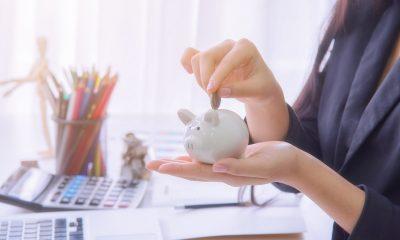 Mulher deposita moeda em um cofre em formato de porco