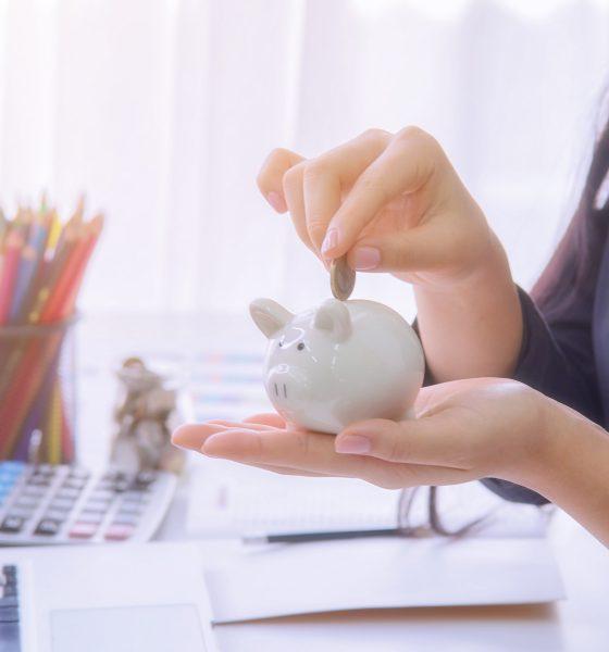 Mulher deposita moeda dentro de um cofre em formato de porco