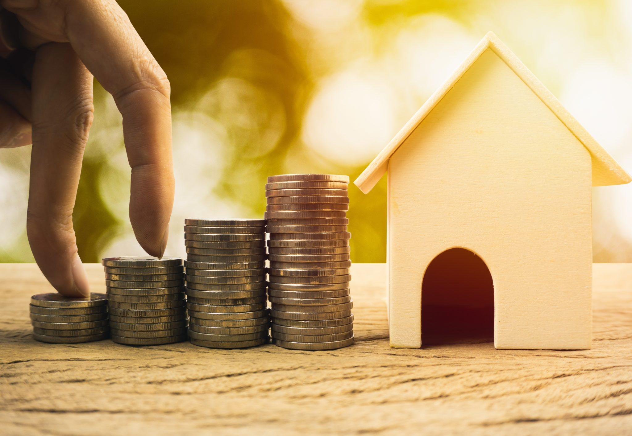 Pilhas de moedas ao lado de uma casa