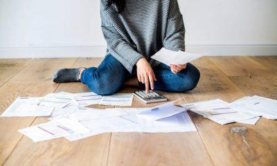 Mulher sentada no chão com calculadora nas mãos cercada de papéis fazendo um planejamento financeiro