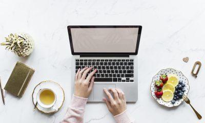 mãos femininas com um laptop em uma mesa com frutas