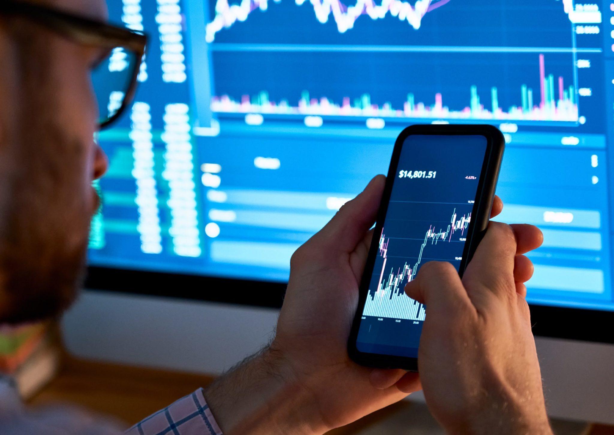Homem verifica no celular análise de negociação de ações