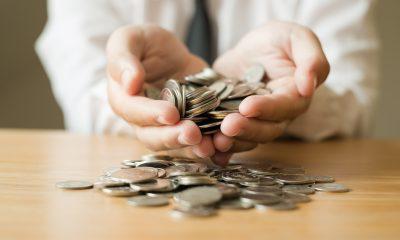 Mãos seguram moedas sobre uma mesa