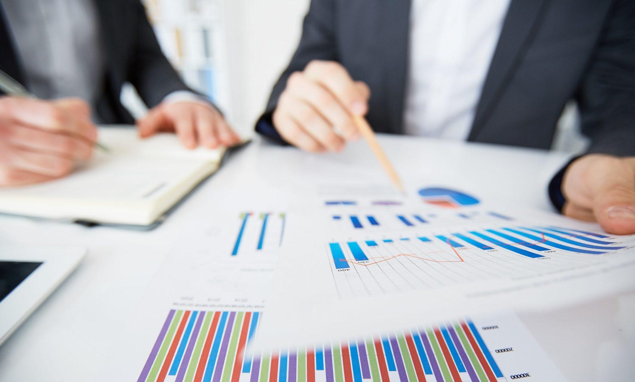 Dois homens simulando um gráfico no papel no boletim focus.