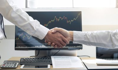 Homens se cumprimentam diante de monitor com gráfico de ações