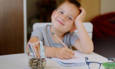 Criança fazendo as contas e guardando dinheiro